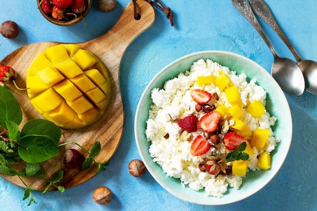 Dietetyczne śniadanie na lato świeży twarożek z truskawkowym mango i orzechami widok z góry