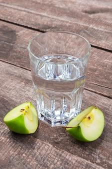 Dietetyczny detox napój z jabłko plasterkami w czystej wodzie i świeżym jabłkiem na drewnianym stole, zamyka up