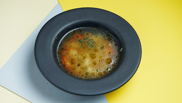 Dietetyczny i zdrowy wywar z kurczaka z warzywami w czarnej misce na kolorowej powierzchni. zamknąć widok