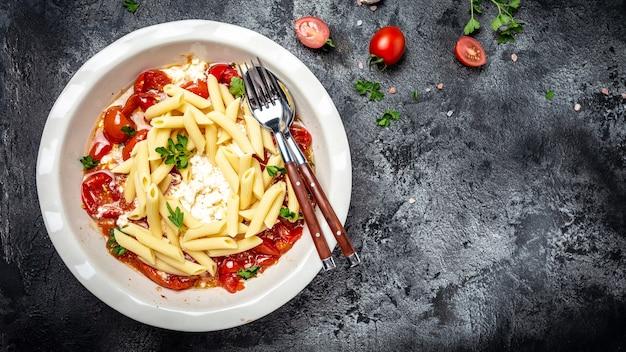 Dietetyczny zdrowy wegański makaron z pomidorami, zielonymi warzywami, serem feta