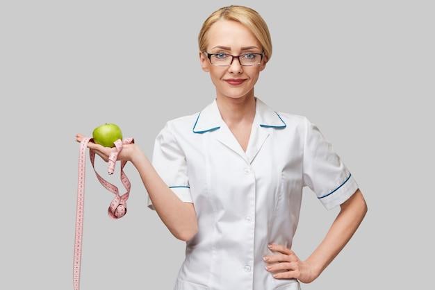 Dietetyk lekarz koncepcja zdrowego stylu życia - trzymając organiczne świeże zielone jabłko i miarkę