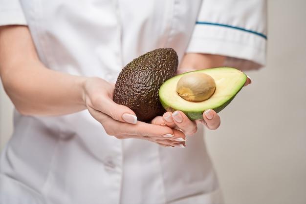 Dietetyk lekarz koncepcja zdrowego stylu życia - trzymanie ekologicznych owoców awokado