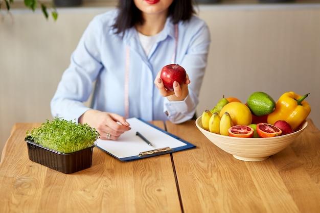 Dietetyk w biurze, trzyma jabłko w hanie