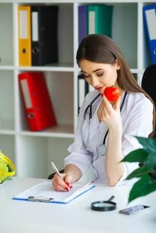 Dietetyk zdrowia siedzi przy stole z owocami i warzywami.