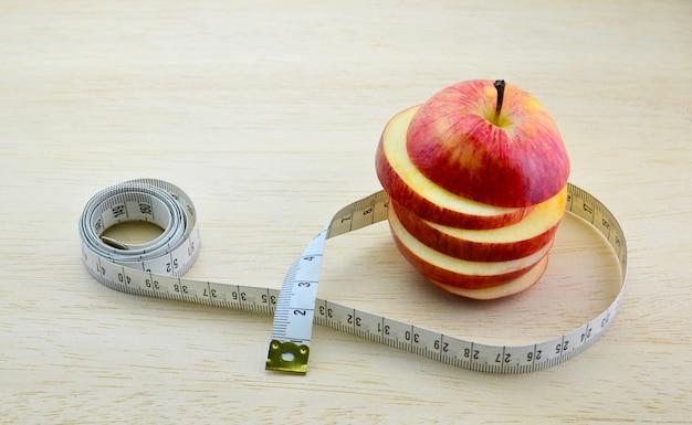 Diety pojęcie pomiarowa taśma z czerwonymi jabłkami na drewnianym stole