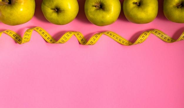 Diety pojęcie z zielonym jabłkiem i pomiarową taśmą w linii na różowym tle