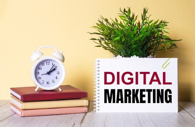 Digital marketing jest zapisany w zeszycie obok zielonej rośliny i białego budzika, który stoi na kolorowych pamiętnikach