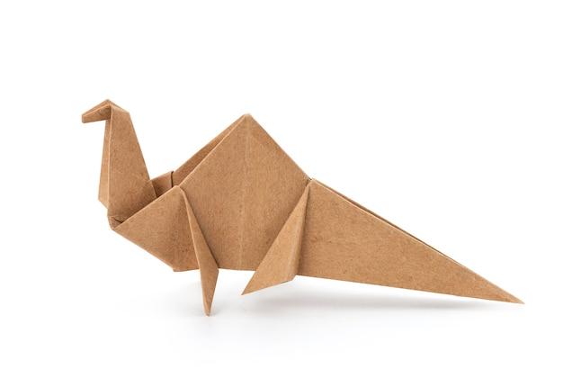 Dinozaur papierowy złożony ze starego papieru na białym tle na białej powierzchni ze ścieżką przycinającą.