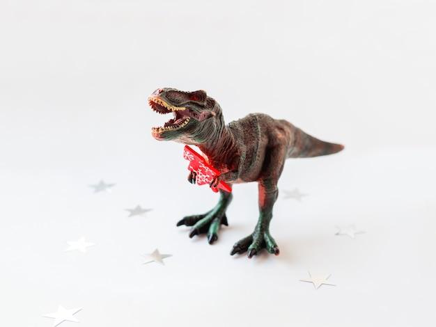 Dinozaur z czerwoną choinką. zabawka plastikowa