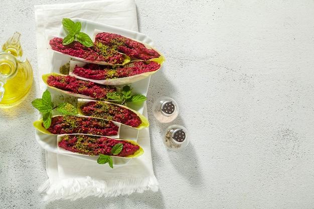 Dip z gotowanych buraków i pistacji w liściach endywii belgijskiej z miętą. zdrowa letnia przekąska