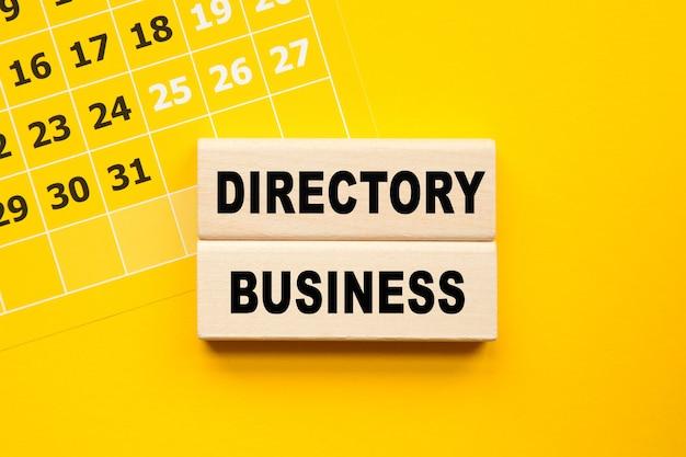 Directory business napis na cubes, żółty długopis na żółtym tle.