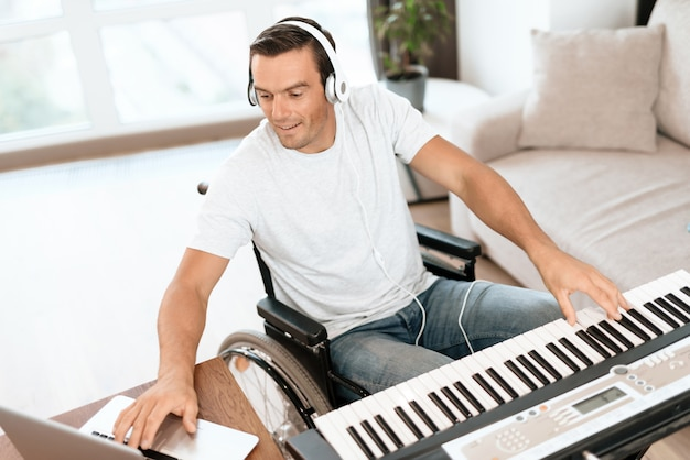 Disabled man composing song with synthesizer