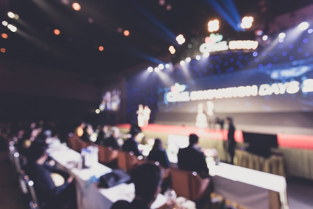 Disfocus głośnika na scenie i dawanie rozmowy na spotkaniu biznesowym.