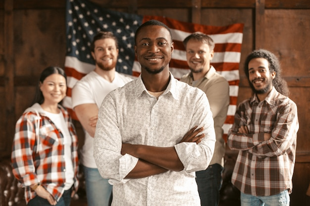Diverse american team standing with american flag