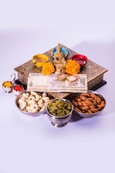 Diwali i przygotowanie do laxmi lub lakshmi pooja z elementami takimi jak diya, banknoty, słodycze, kwiaty, przekąski, haldi i kumkum