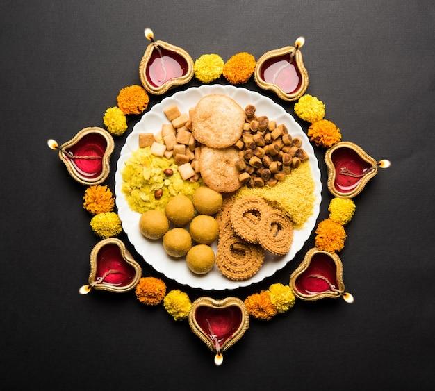 Diwali rangoli z indyjskimi słodkimi przekąskami i diya