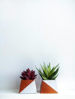 Diy betonowe doniczki, kształt piramidy z zielonymi i czerwonymi sukulentami na białej drewnianej półce na białej ścianie z miejscem na kopię. dwie unikalne donice cementowe pomalowane na kolor miedziany, pionowy.