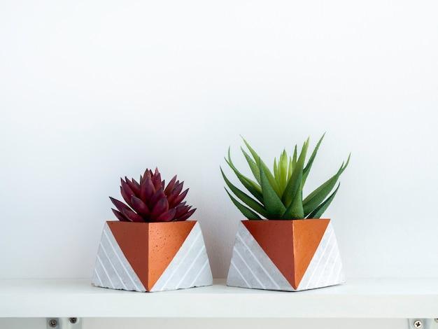 Diy betonowe doniczki, kształt piramidy z zielonymi i czerwonymi sukulentami na białej drewnianej półce na białej ścianie z miejscem na kopię. dwie unikatowe donice cementowe pomalowane na kolor miedzi.