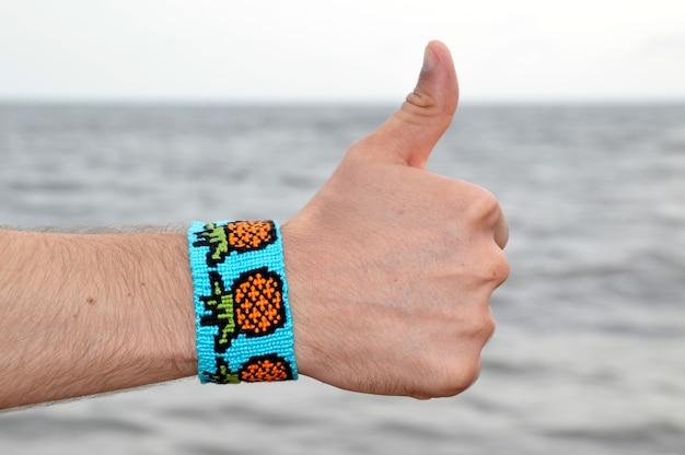 Diy bransoletka przyjaźni z wzorem ananasa na dłoni mężczyzny na morzu