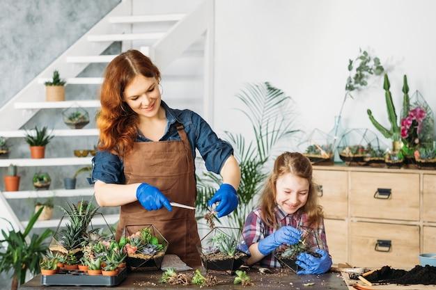 Diy florarium. ogrodnictwo domowe. matka i córka ciesząc się sadzeniem sukulentów, zabawą, uśmiechem.