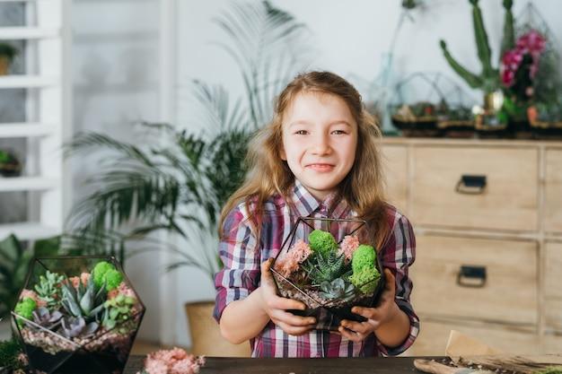 Diy florarium. ręcznie robiony naturalny prezent. dziewczyna trzyma szklany geometryczny wazon z zielonymi sukulentami, uśmiechając się.