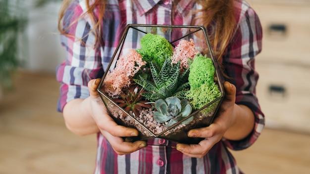 Diy florarium. ręcznie robiony naturalny prezent. przycięte zdjęcie dziewczyny trzymającej szklany wazon geometryczny z ozdobnym układem kwiatowym.