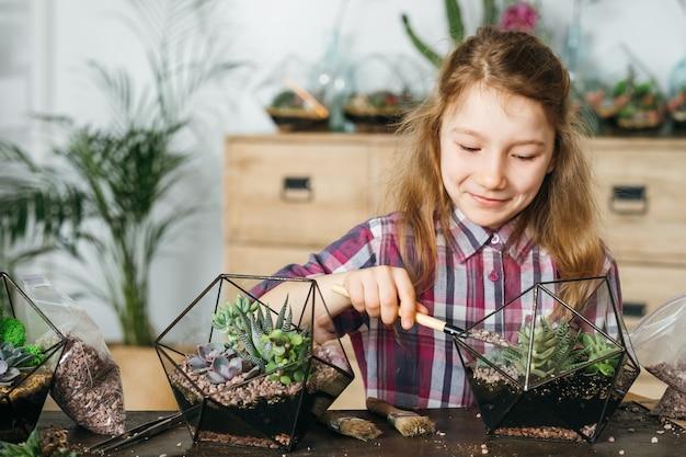 Diy florarium. zajęcia z ogrodnictwa domowego. dziewczyna korzystających z sadzenia sukulentów w szklanych wazonach geometrycznych. rozmycie tła wnętrza.
