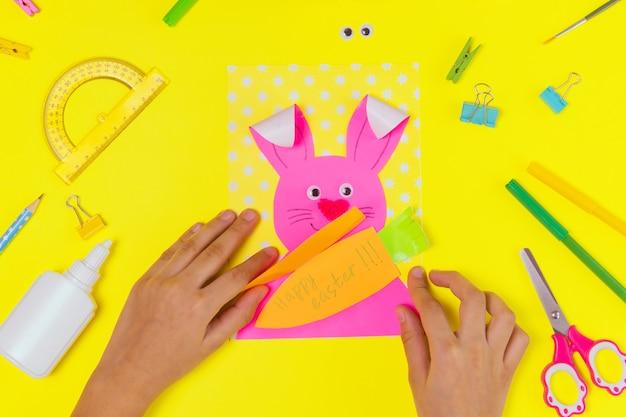 Diy i kreatywność dzieci. instrukcja krok po kroku: utwórz kartkę wielkanocną z zajączkiem i marchewką. ręcznie robione rękodzieło wielkanocne dla dzieci. widok z góry krok 5