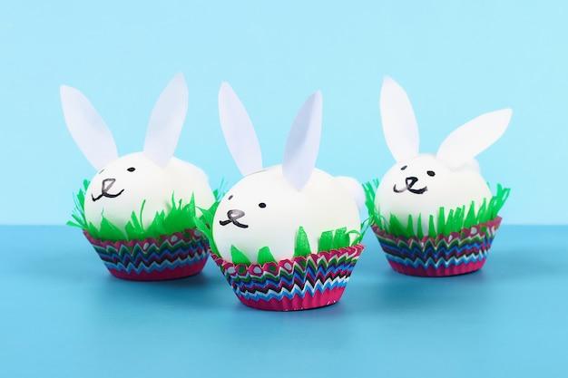 Diy królik od easter jajek na błękitnym tle. pomysły na prezenty, wystrój wielkanoc, wiosna. wykonany ręcznie.