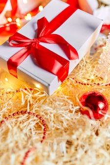 Diy pakowanie prezentów na prezent bożonarodzeniowy białe pudełko z czerwoną wstążką, świąteczna dekoracja na stole.
