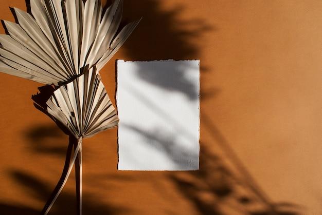 Diy paper pusty biały plakat zaproszenia ślubne z suszonymi liśćmi palmowymi na teksturowanym stole z terakoty. elegancki, nowoczesny szablon tożsamości marki. leżał płasko, widok z góry