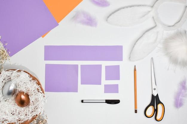 Diy papierowy królik na wielkanoc. instrukcje krok po kroku. widok z góry. krok 1 przygotuj kolorowy papier.