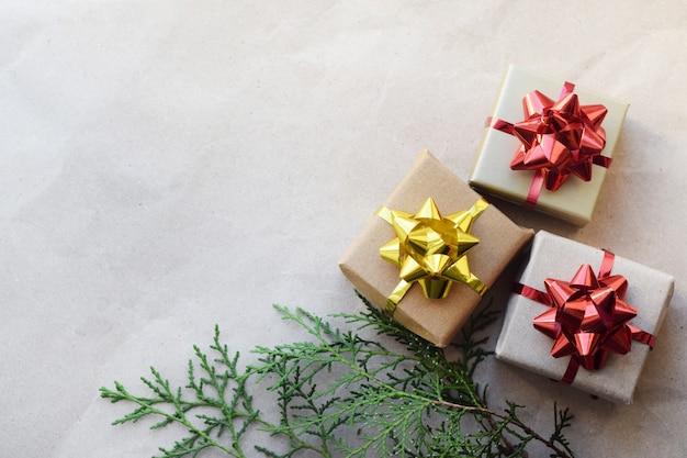 Diy pudełka na prezenty świąteczne z kokardkami w domu. pudełka z prezentami na tle papieru rzemieślniczego i gałęzi jodły