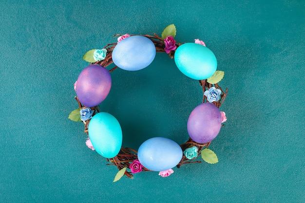 Diy wielkanocny wianek z gałązek, malowanych jajek i sztucznych kwiatów na zielonym tle.