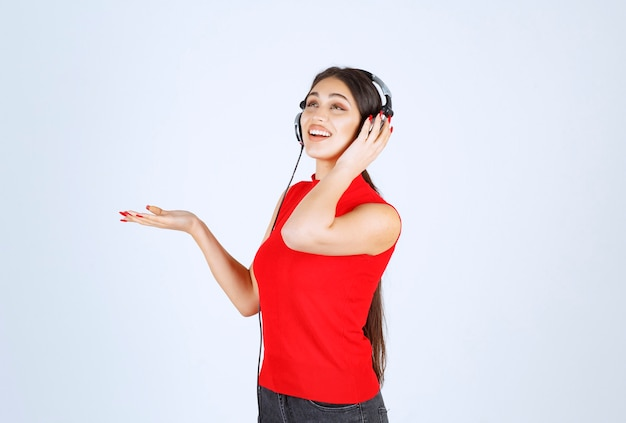 Dj dziewczyna w czerwonej koszuli ze słuchawkami wskazując coś lub pokazując coś w jej ręce.