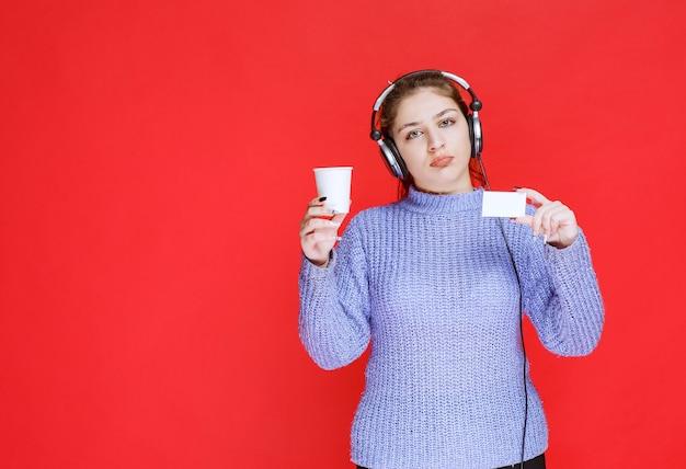 Dj dziewczyna z filiżanką kawy w ręku pokazując jej wizytówkę.