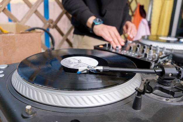Dj gra miksowanie muzyki na gramofonie winylowym na imprezie. nierozpoznawalny młody biały dj przy biurku muzycznym podczas dj setu na tarasie modnego baru młodzieżowego. moskwa, rosja - 06.05.2021
