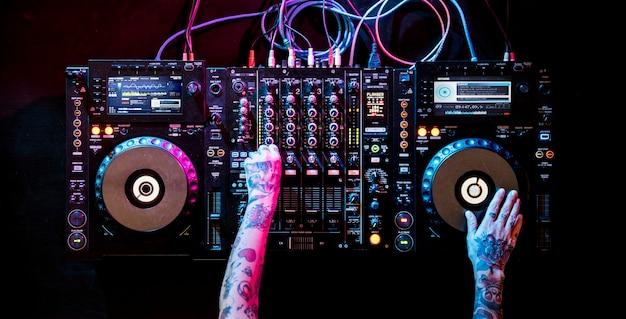 Dj gra muzyka w mikserze dźwięku w nocnym klubie