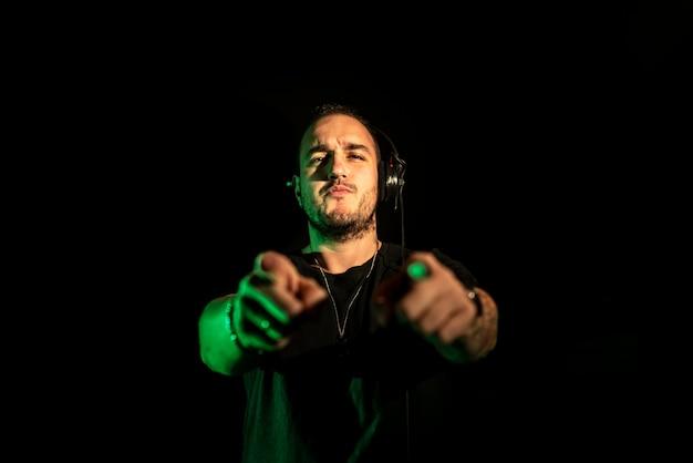 Dj grający muzykę house i techno w nocnym klubie. miksowanie i sterowanie muzyką.