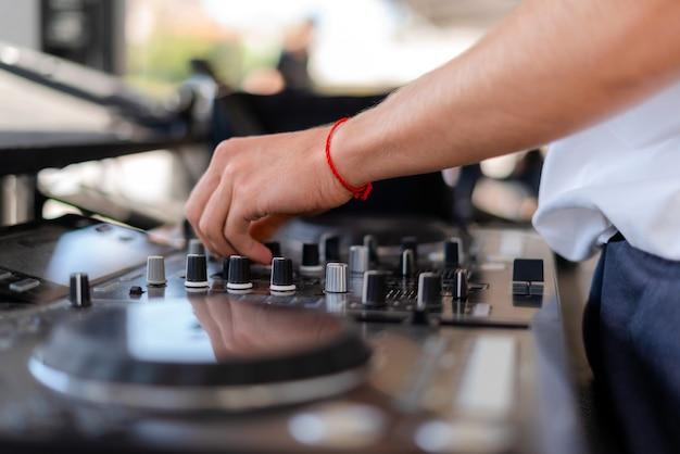 Dj grający muzykę na imprezie plenerowej. osoba obsługująca mikser na festiwalu muzycznym.