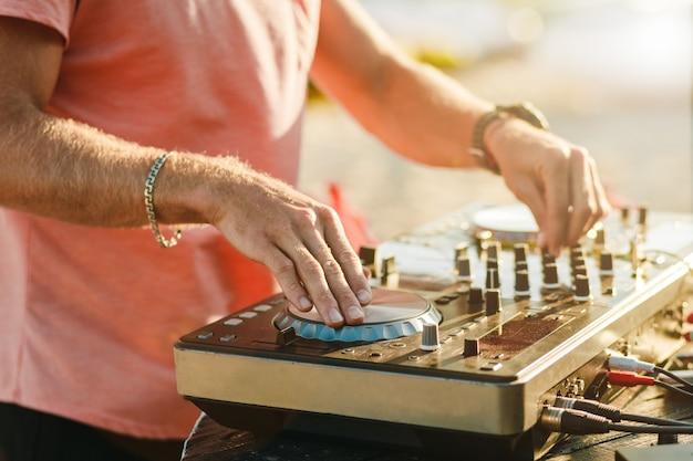 Dj grający na letniej imprezie na konsoli dj
