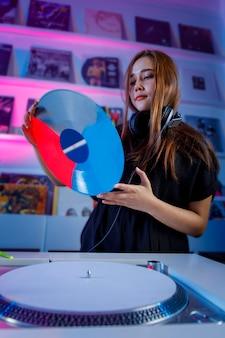 Dj latina mezclando musica en una tienda de discos con un tornamesa y discos de vinil