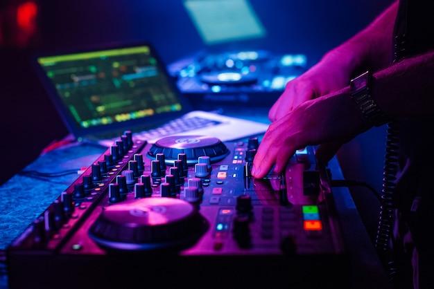 Dj miksuje muzykę elektroniczną z rękami na kontrolerze muzycznym