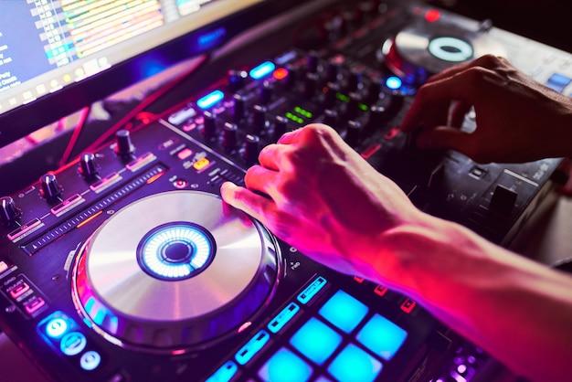 Dj miksuje utwór w nocnym klubie na imprezie