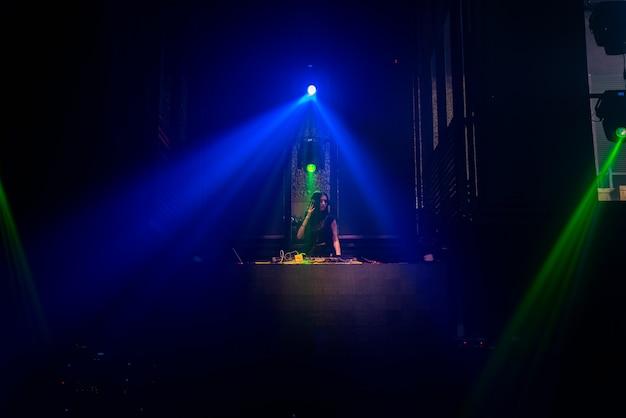 Dj na scenie w nocnym klubie disco miksuje beat muzyki techno