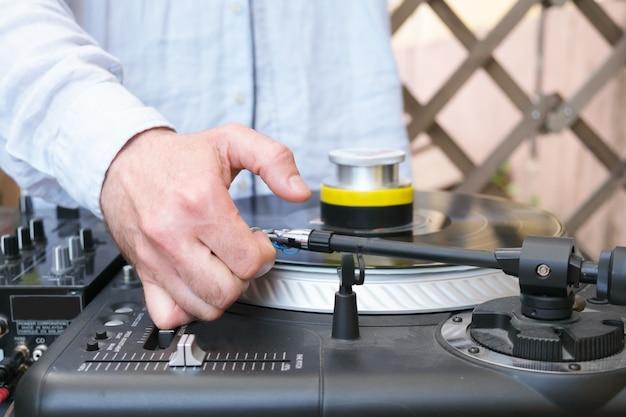 Dj reguluje igłę na gramofonie. ręka mężczyzny dj w niebieskiej koszuli. nierozpoznawalny młody biały dj przy biurku muzycznym podczas dj setu na tarasie modnego baru młodzieżowego.