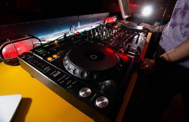 Dj rozpoczyna pracę na zmianę. mężczyzna w białej koszulce stojący w pobliżu gramofonów i włącza go. praca w nocnym klubie. ciemny pokój na tle. dobra koncepcja muzyczna. męski dżokej.