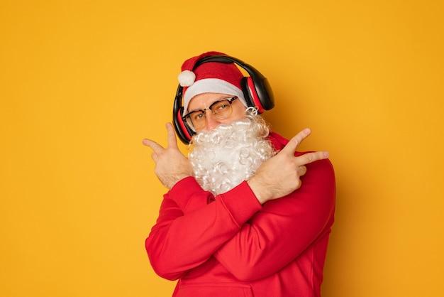 Dj święty mikołaj w słuchawkach. świąteczne piosenki i muzyka. żółte tło.