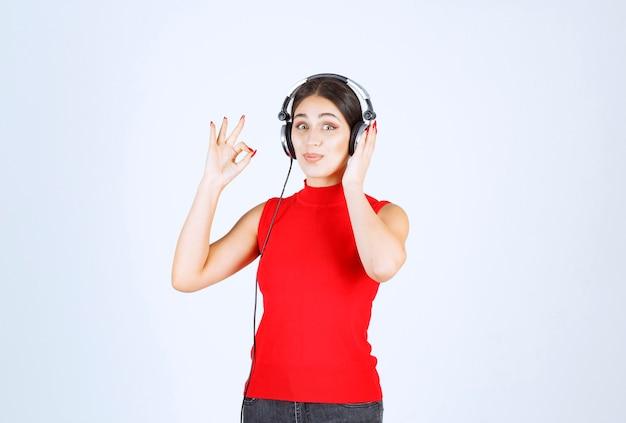 Dj w czerwonej koszuli w słuchawkach i słuchając muzyki.