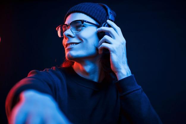 Dj w swojej pracy. studio strzałów w ciemnym studio z neonowym światłem. portret poważnego mężczyzny